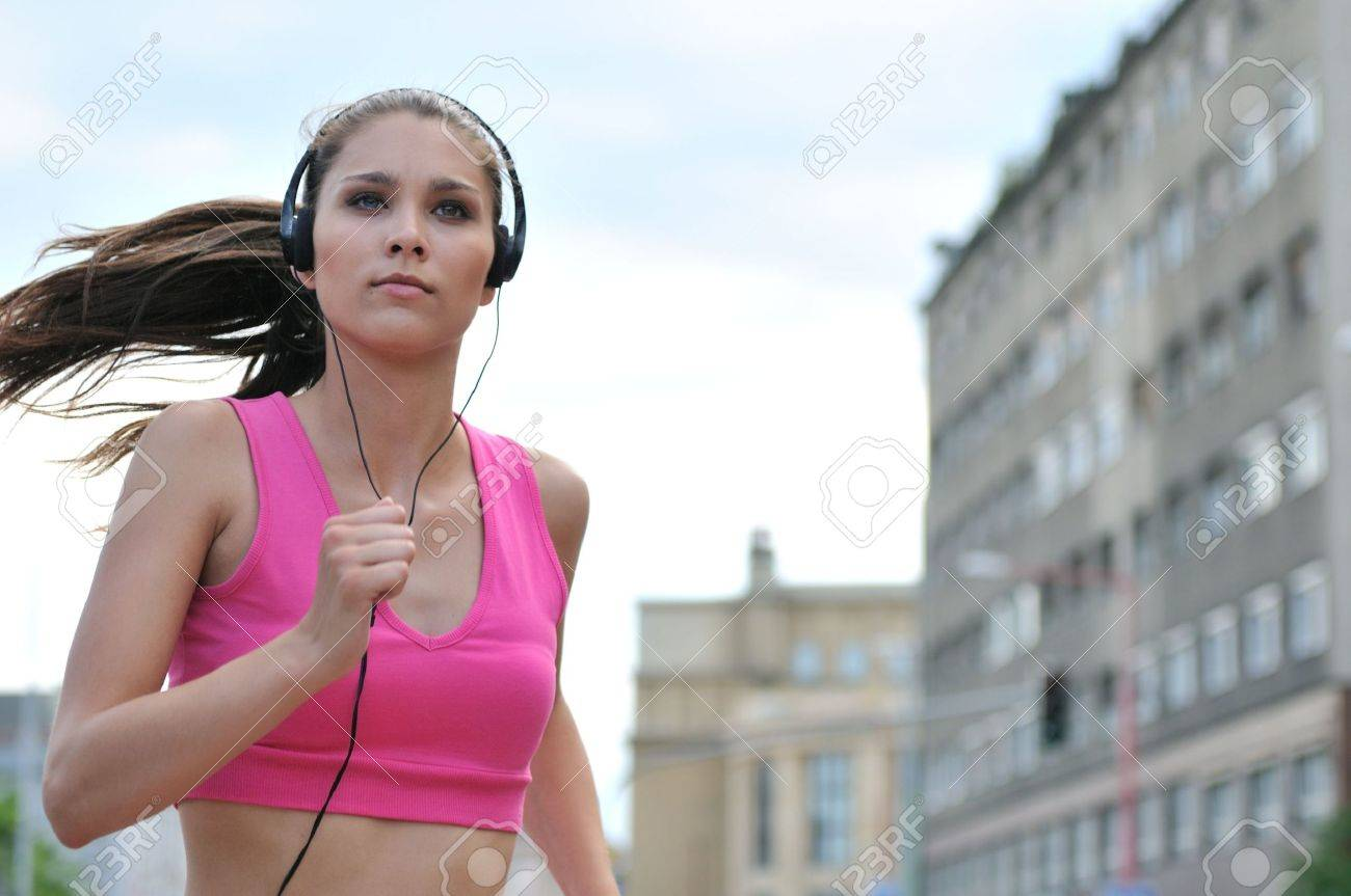 Person (young beautiful woman) listening music running (jogging) in city street Stock Photo - 5237267