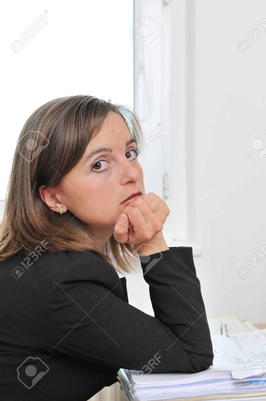 Bored business woman sitting at table with papers on workplace Stock Photo - 5509469