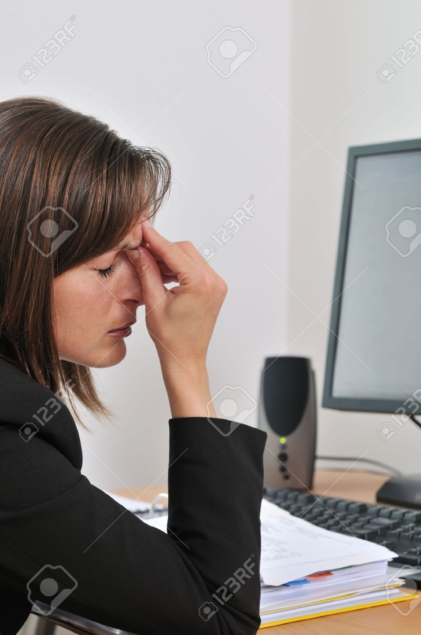 Young business person (woman) has headache and tired eyes are closed - computer and papers on work table Stock Photo - 5509457