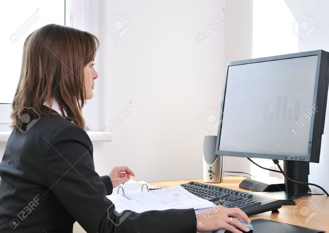 Business person (young woman) works at table with computer - office interior Stock Photo - 5543852
