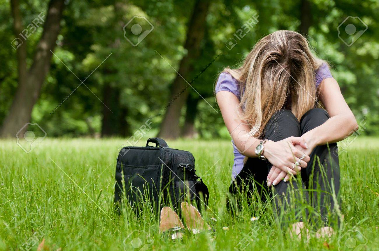 Young depressed business woman siting in grass - notebook bag and shoes lying next - 7201637