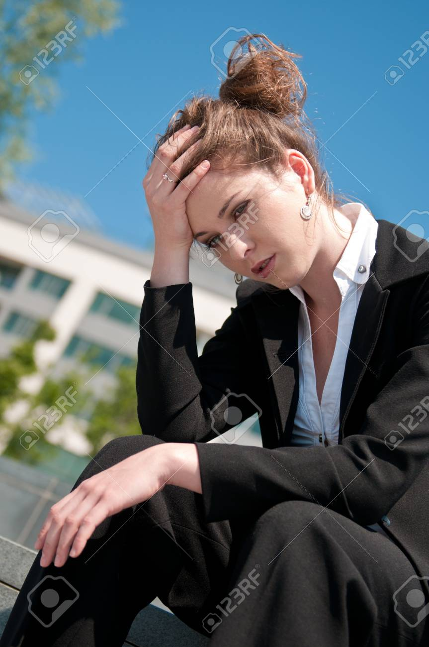 Young depressed business woman siting outdoors - building in background Stock Photo - 7565265