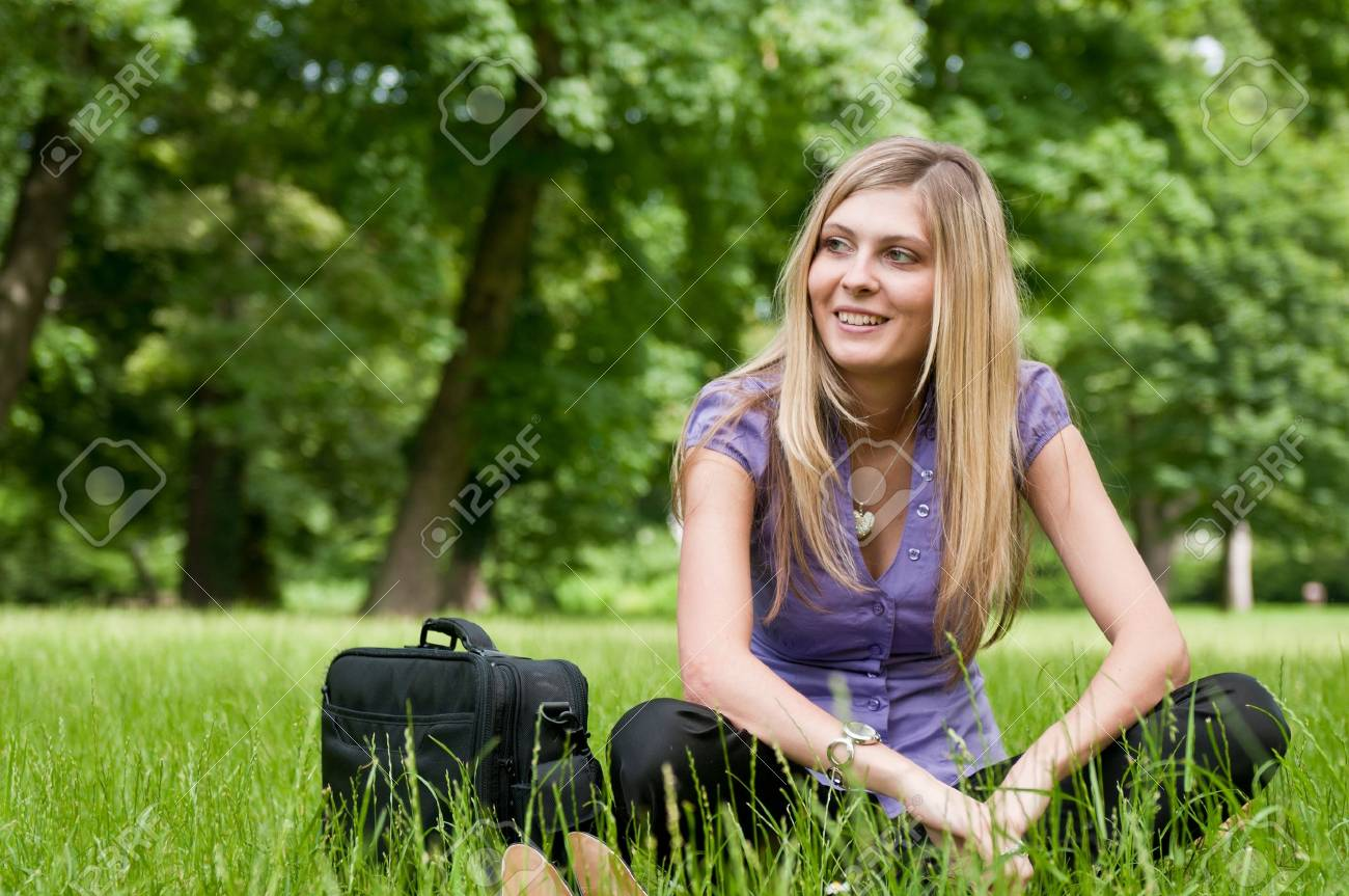 Young smiling business woman siting in grass and relaxing after work Stock Photo - 7699689