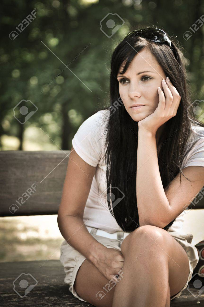 Young sad and pensive woman siting on bench in park - detail Stock Photo - 7807659
