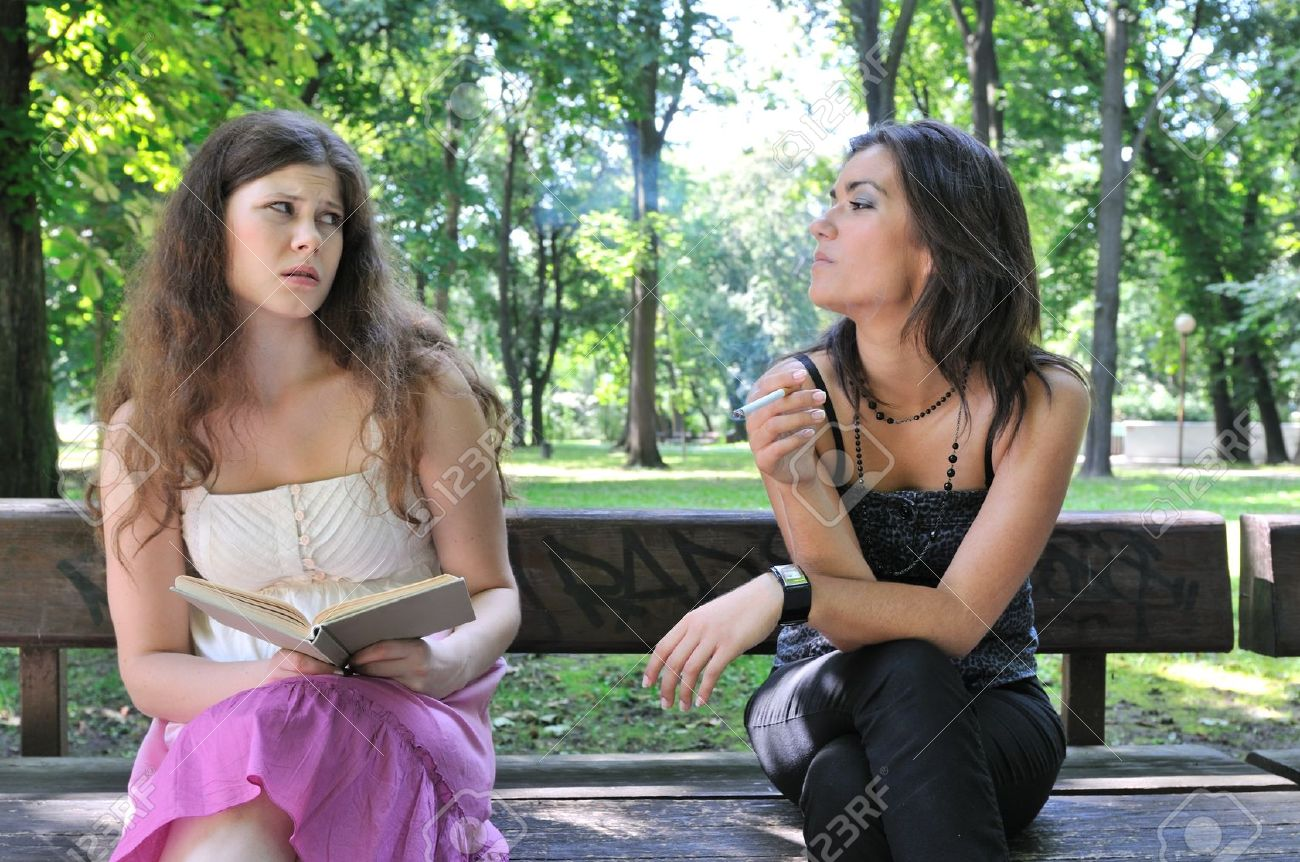 Two young people outdoors on bench in park, one teenager smoking cigarette annoys another girl Stock Photo - 8602269