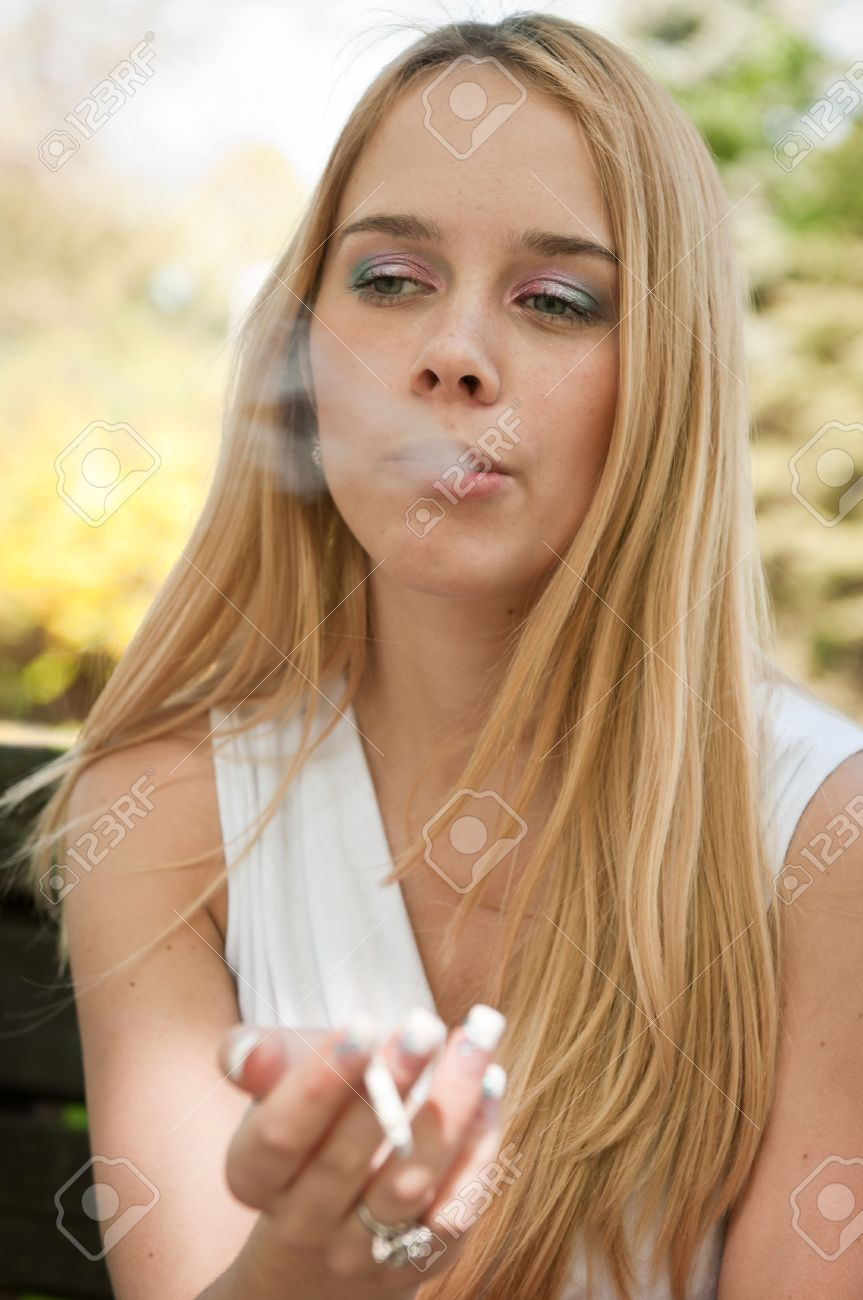 Portrait of young woman smoking cigarette outdoors blowing smoke Stock Photo - 9455120
