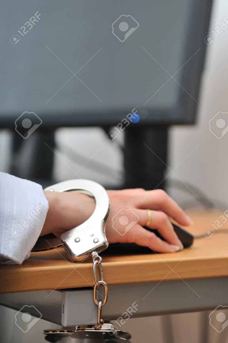 Detail of business person hand tied with handcuffs to workplace, keyboard and monitor in background. Stock Photo - 10173426