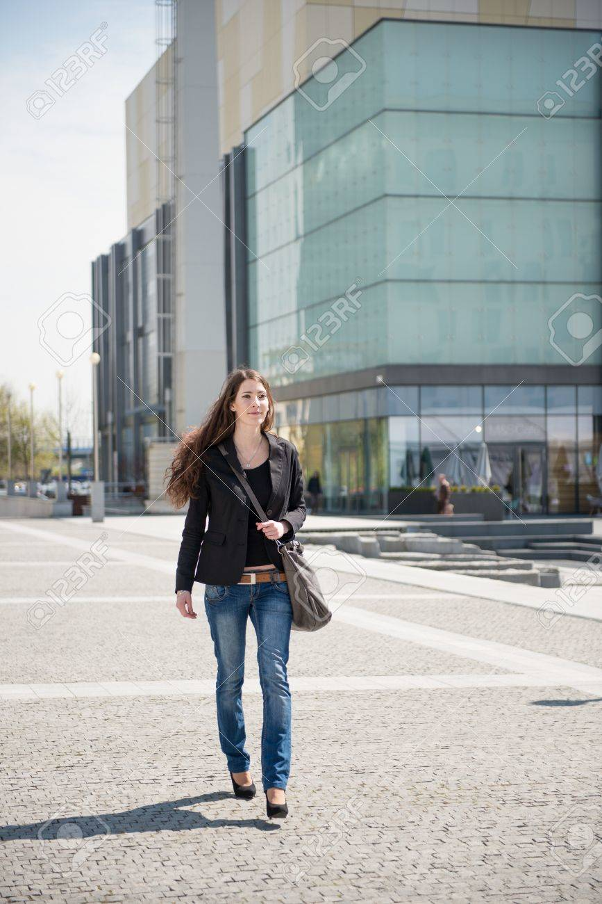 Young woman with laptop bag walking street Stock Photo - 13649504