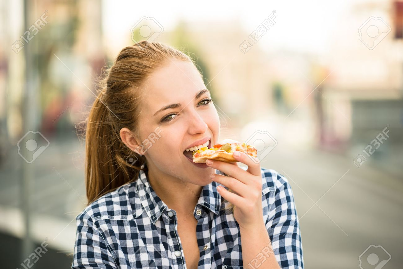 Teenager lifestyle - young woman eating pizza outdoor in street - 51640454