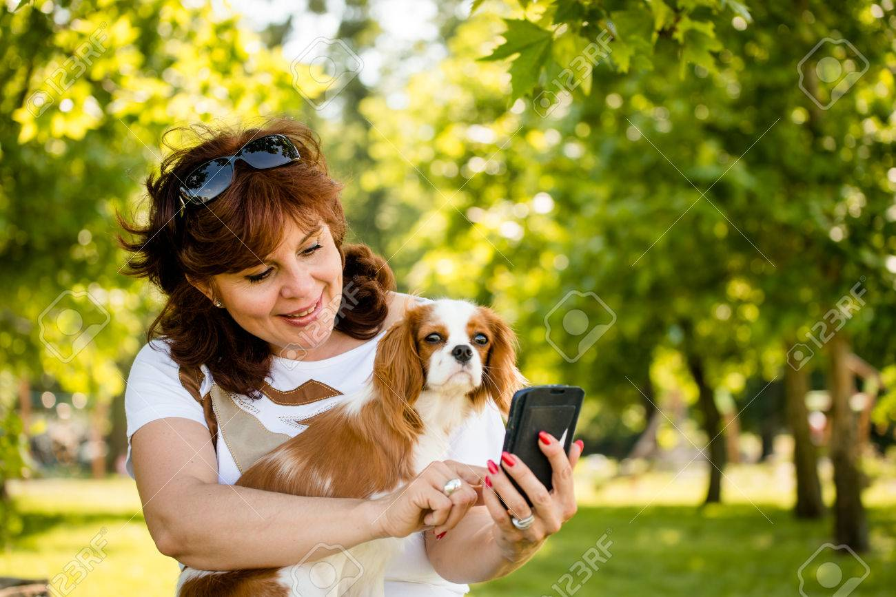mature woman showing something to her cavalier dog on smartphone