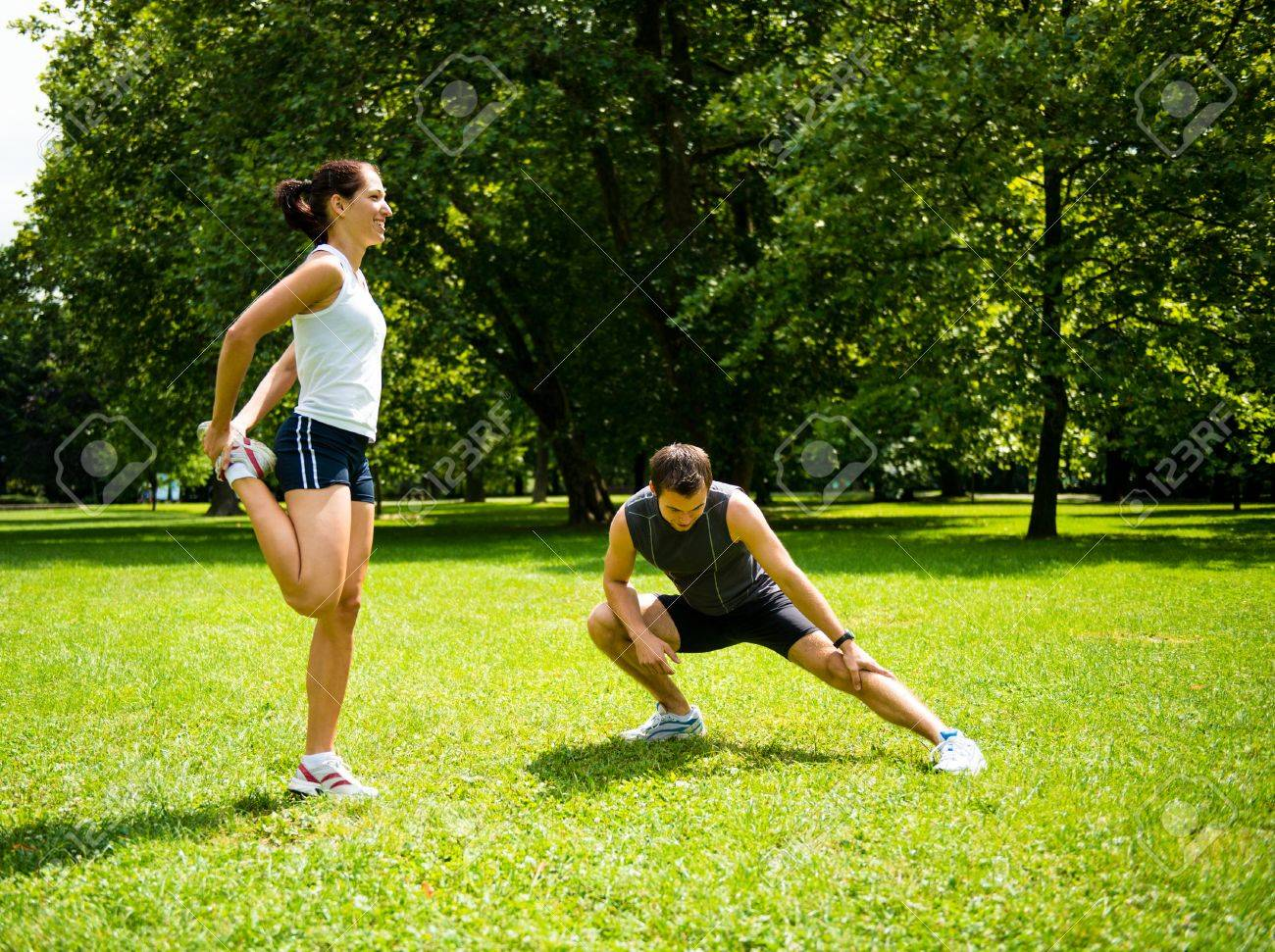Young couple exercising and stretching muscles before sport activity - outdoor in nature - 52577735
