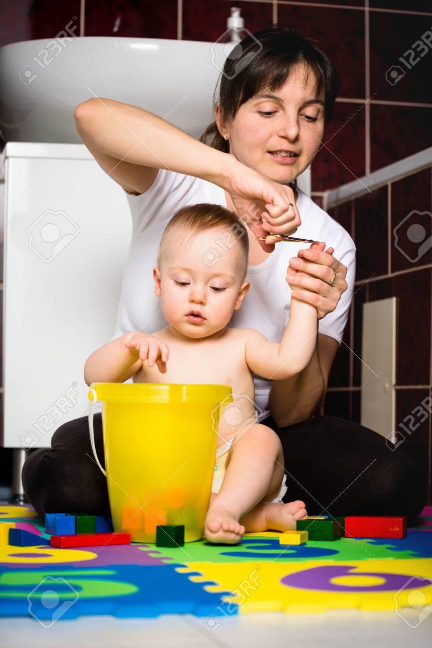 Mère Couper Les Ongles De Son Enfant Tout Bébé Joue Avec Des Jouets