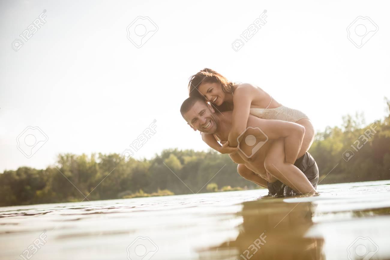 Naked woman piggyback man