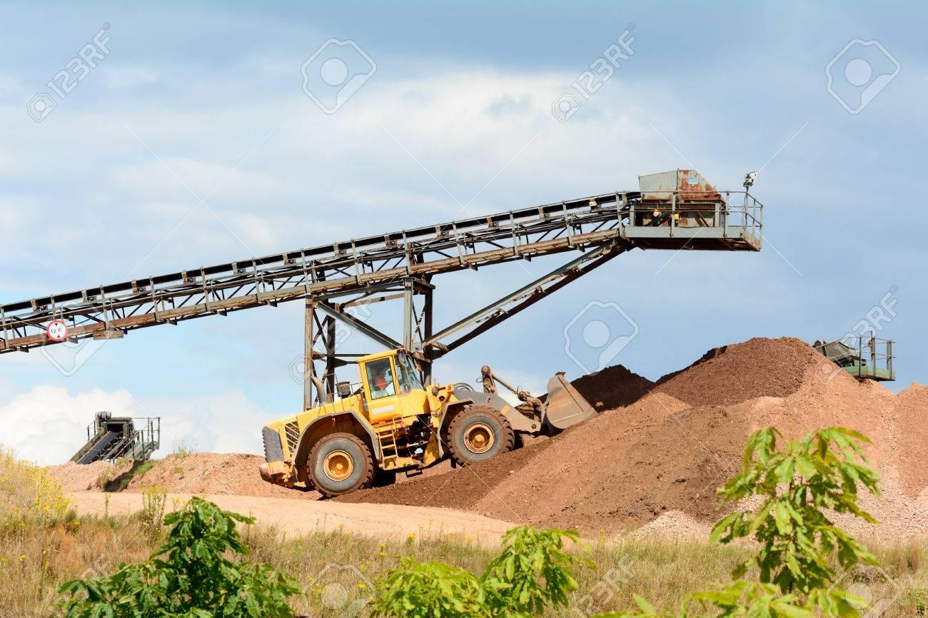 Mining machines and conveyor belts making piles of rock