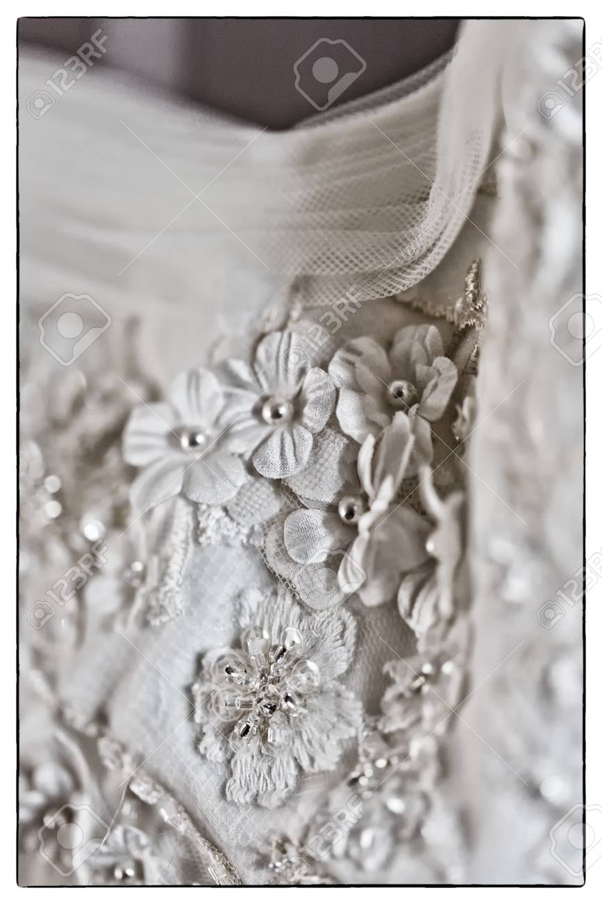 A Macro Photo Of A Detailed White Wedding Dress With White Flowers