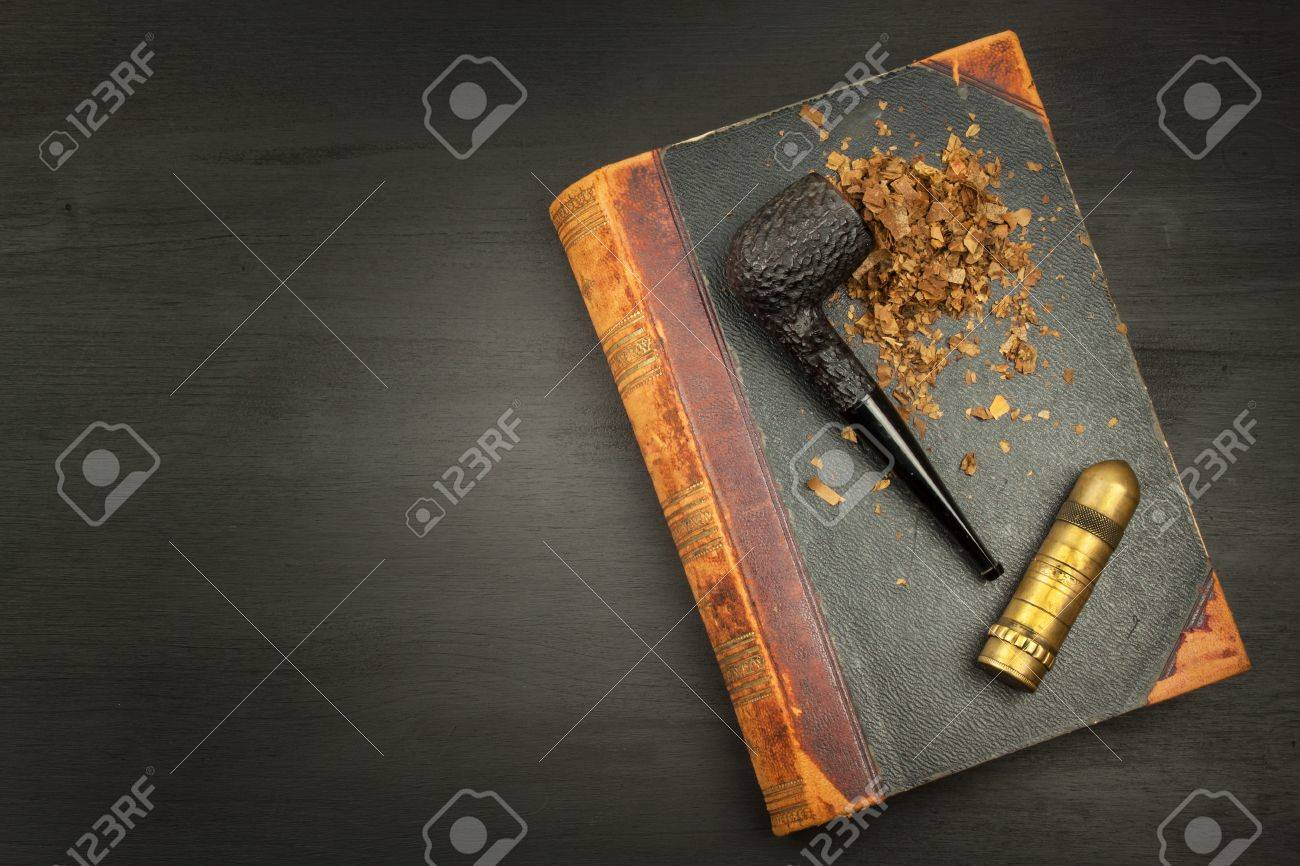 Smoking pipe and antique books  Tobacco pipe on ancient books