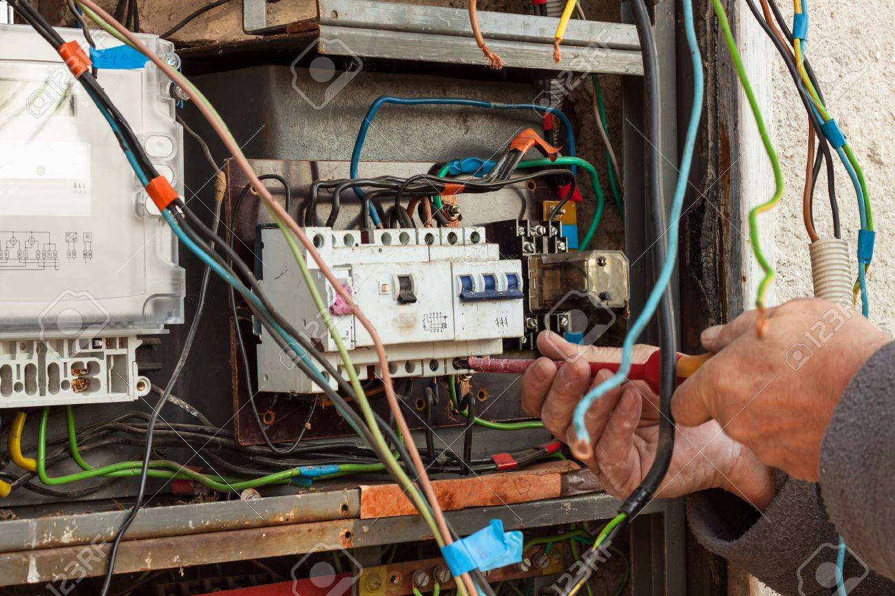 Repair of old electrical switchgear. An electrician replaces.. on