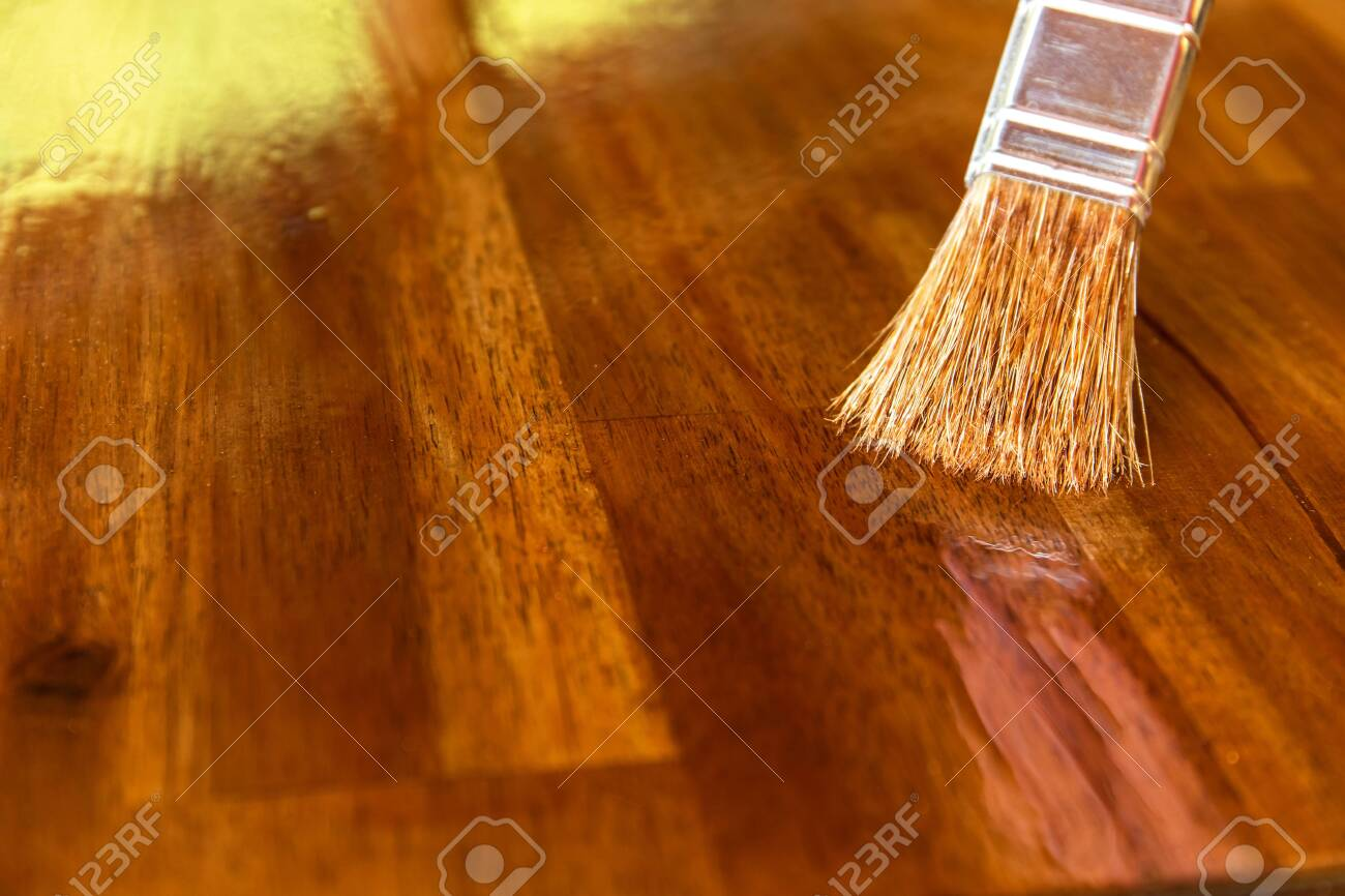 Applying protective oil on a wooden furniture. Varnishing the table top of acacia wood. Close-up view of a paintbrush. Housework. - 146710377