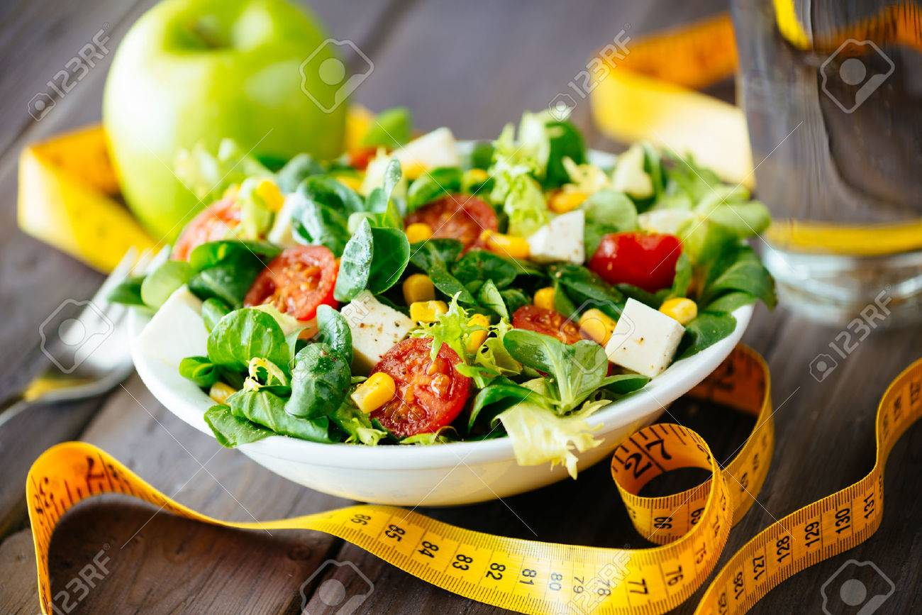 Fitness salad and measuring tape on rustic wooden table Mixed greens, tomatos, diet cheese, olive oil and spices for healthy lifestyle concept - 25934033