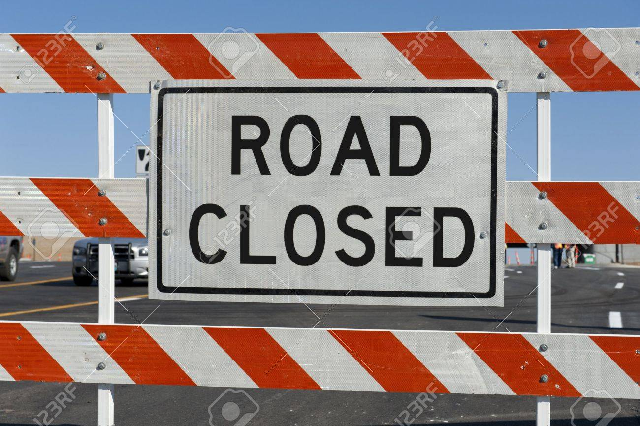Worn Road Closed Sign in front of street being repaired Stock Photo - 8370647
