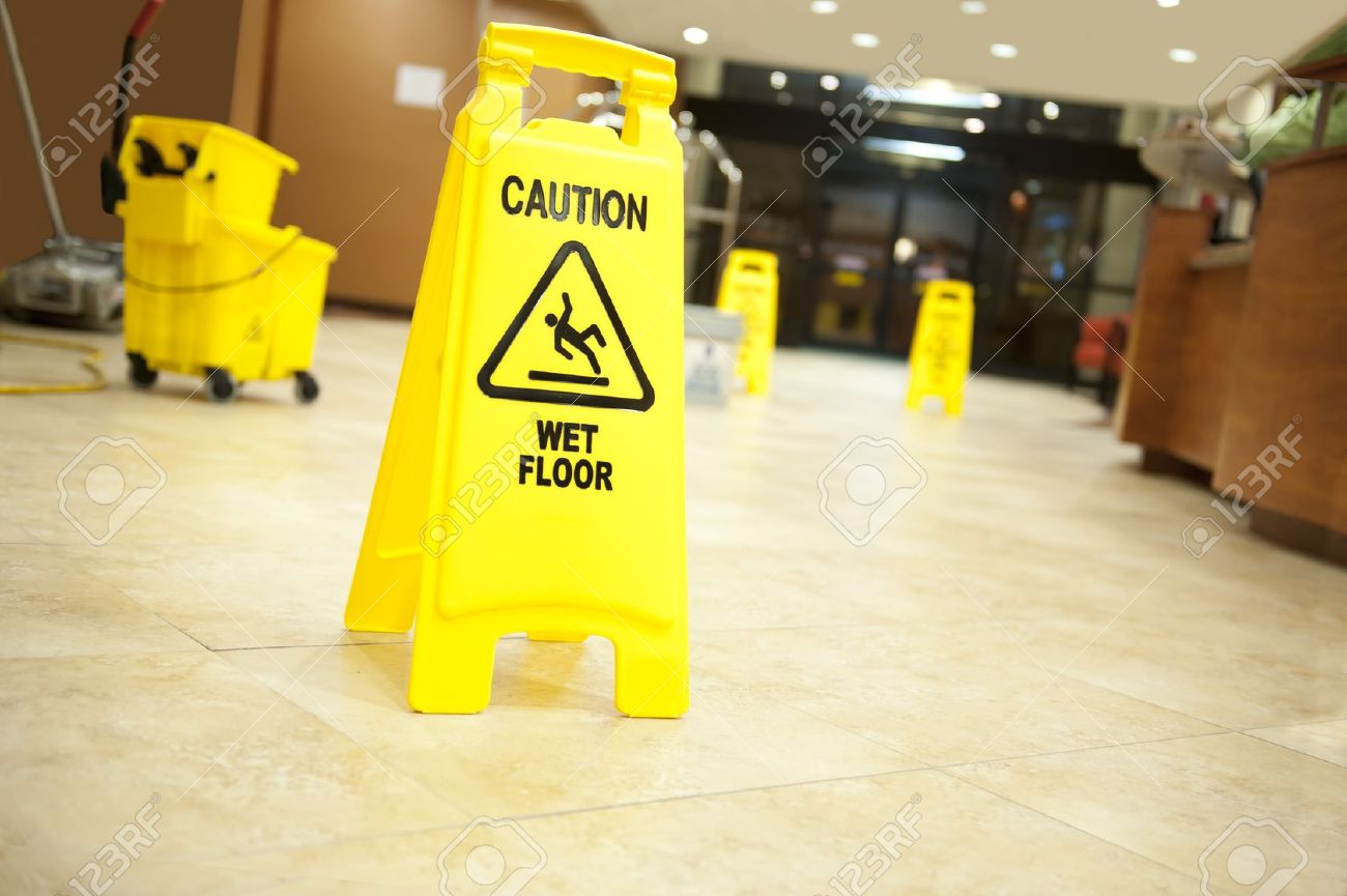 """Lobby floor with mop bucket and """"caution wet floor"""" signs, selective focus on nearest sign - 10606106"""