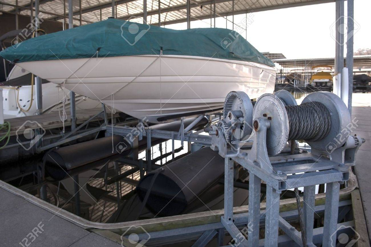 Expensive pleasure boat safely stored under canopy on a hyrdolic lift in a dock Stock Photo - 16918797