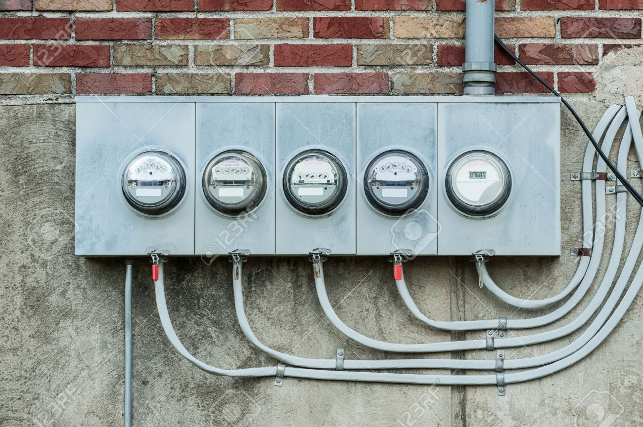 a series of electric meters line the wall of an apartment building stock  photo - 29875551