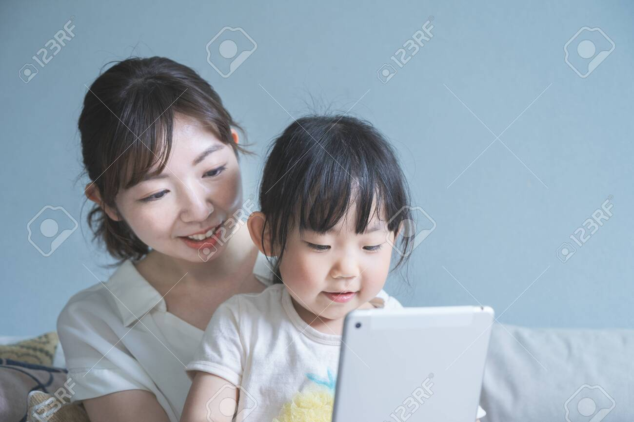Mom and daughter sitting on a sofa and operating a tablet device - 149387235
