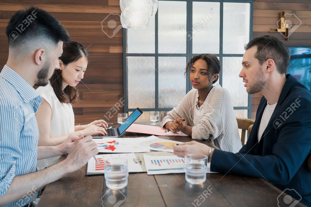 Businessmen of various races meeting in a casual office space - 153629867