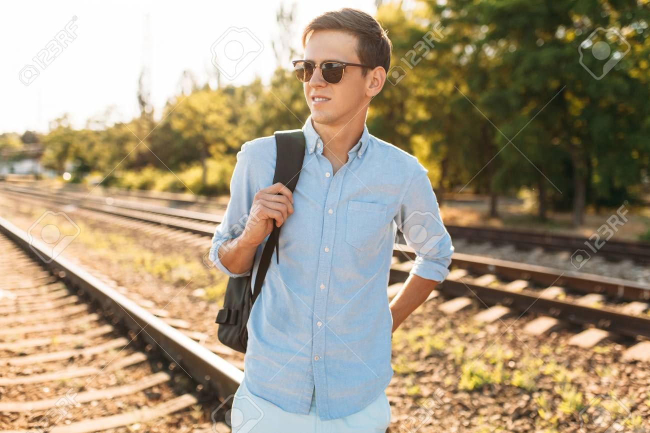 3318177e0540 Beautiful stylish guy with glasses, posing on the rails of the train at  sunset,