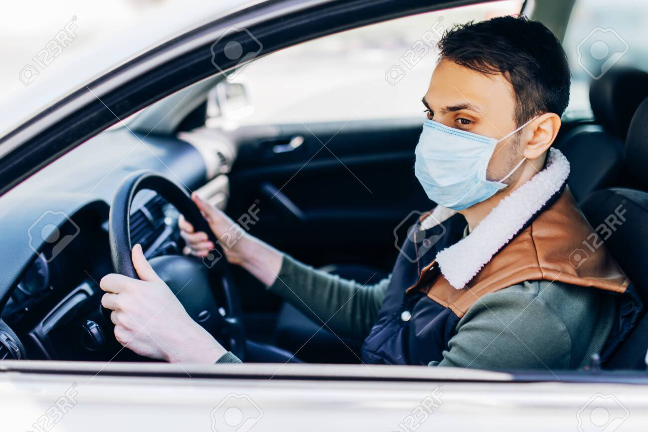 Beautiful young masked man sitting in a car, protective mask against coronavirus, driver on a city street during a coronavirus outbreak, covid-19 - 145417601