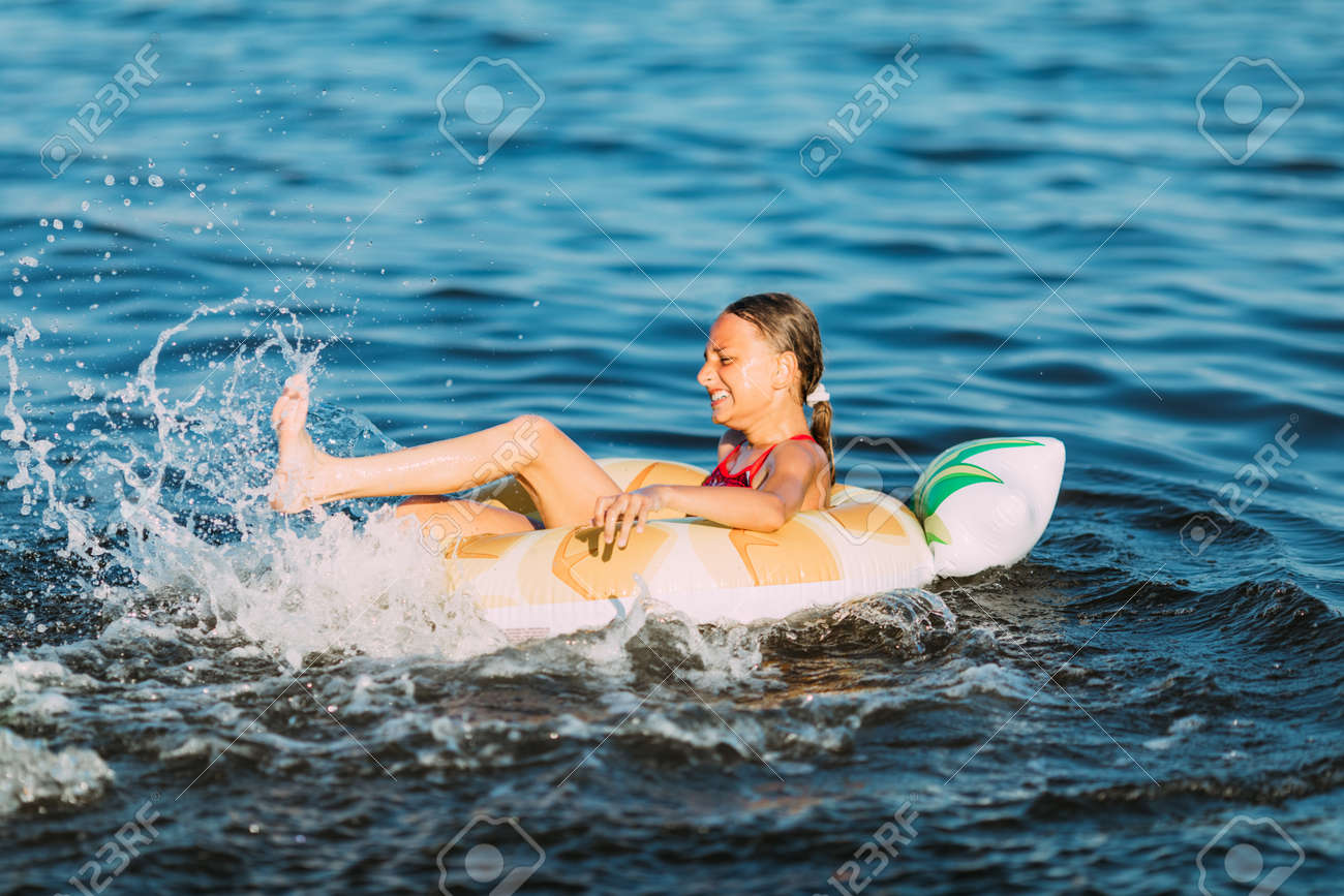 Happy child on an inflatable circle floating on the sea, Summer holidays with children. Swimming equipment and clothing for children. - 151460789