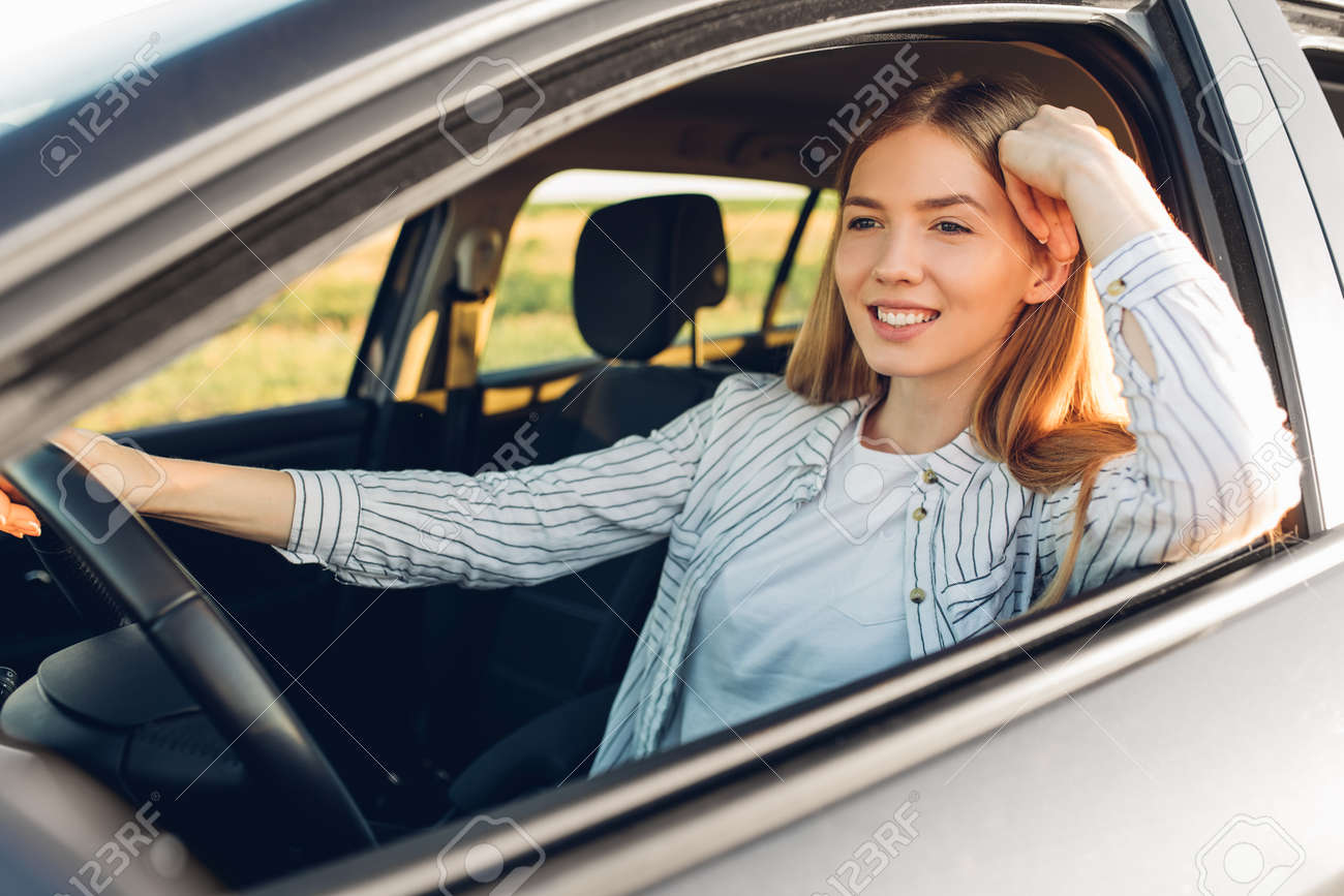 Beautiful young happy smiling woman driving her new car at sunset - 166443765