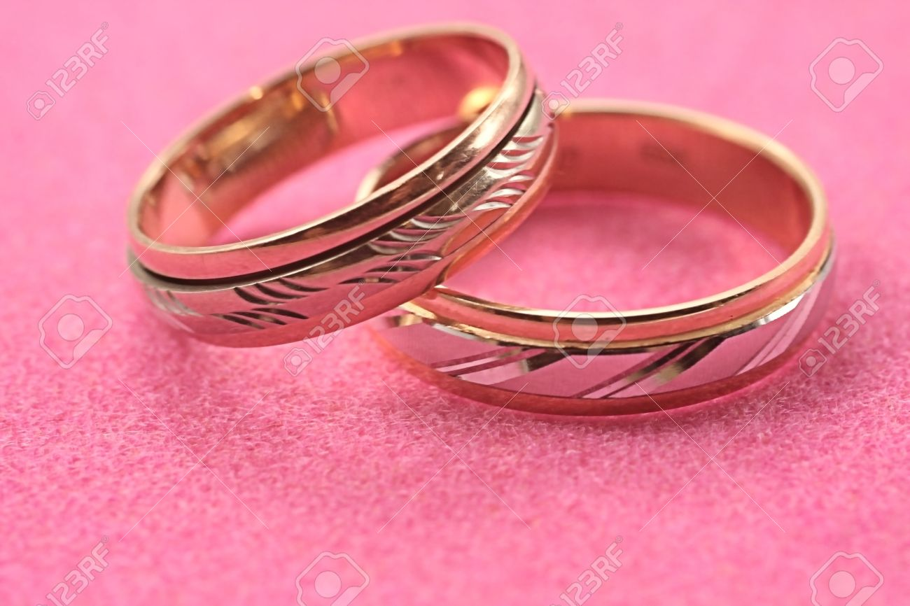Gold Wedding Rings Without Stones On A Pink Background Stock Photo ...