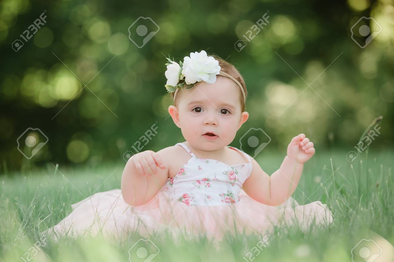 Cute one year old caucasian girl outside in grass wearing a pink summer  dress and floral