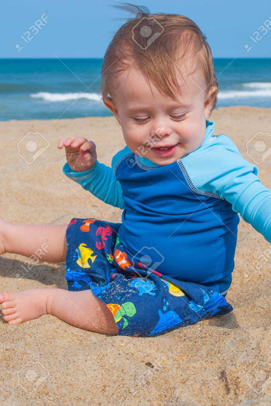 458b1b0ef Baby Boy Wearing Blue Shirt Playing in the Sand at the Beach Stock Photo -  93745781