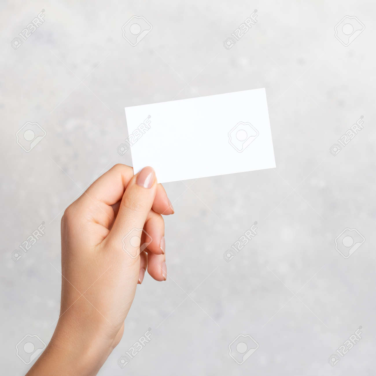 Female hand holding a blank business card, cutaway on gray concrete background with copy space. - 156369746