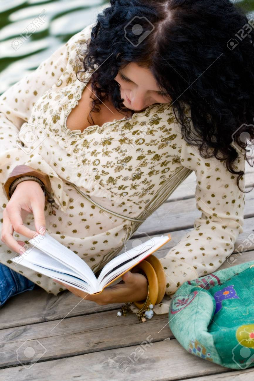 outdoor portrait of a beautiful woman reading a book Stock Photo - 5070417
