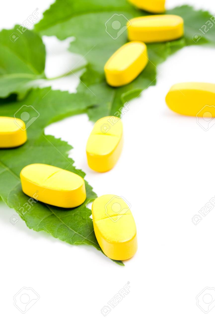 yellow vitamin pills over green leaves on white background Stock Photo - 6971843