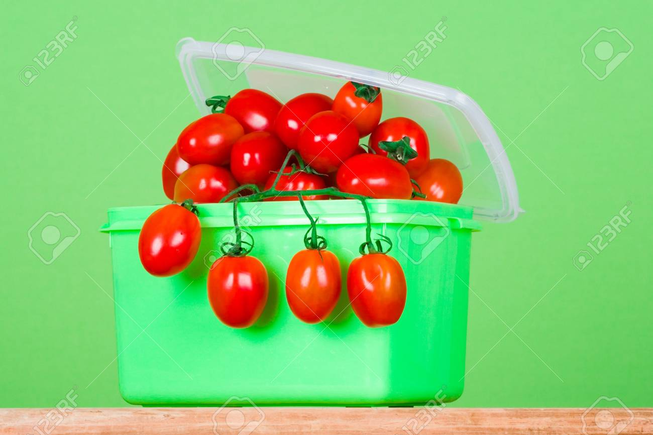container with fresh tomatoes on green background Stock Photo - 7303724