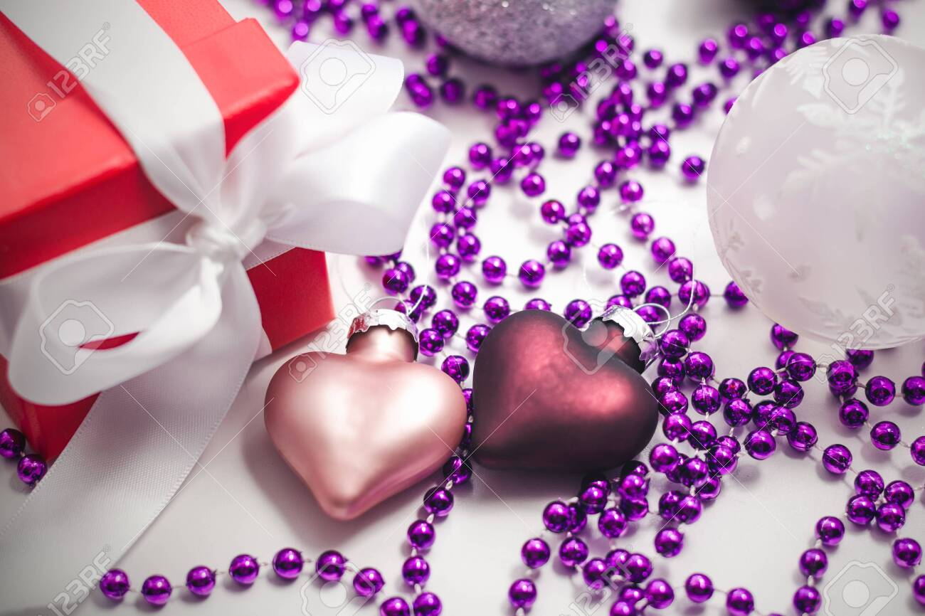 Two glass Christmas decorations in the shape of a heart of pink and purple, a red gift box with a white ribbon and lilac beads on a light surface - 133797113