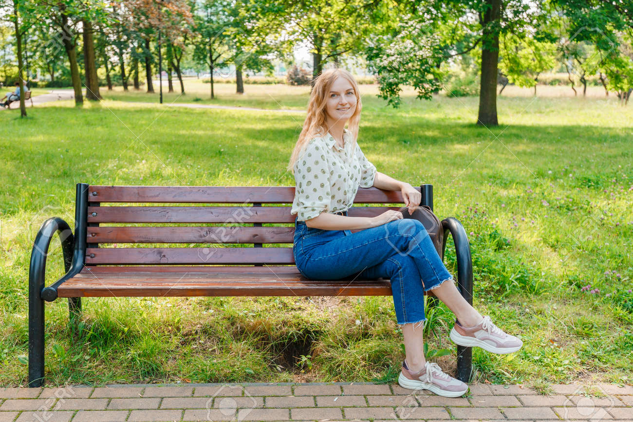 The beautiful young woman sits on a bench - 155177292