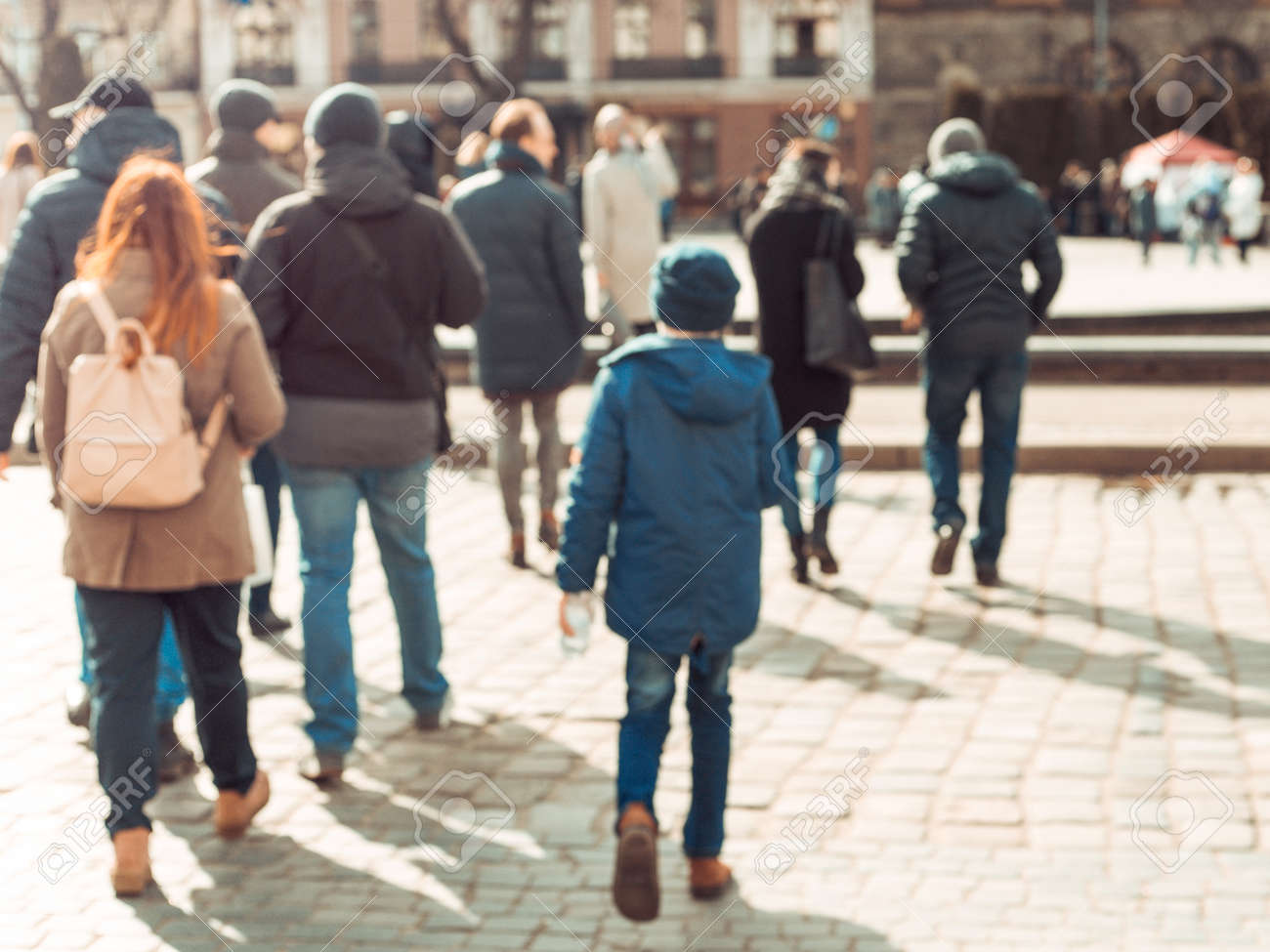 Blurred background. Blurred people walking through a city street. The photo is made out of focus, no faces are recognisable - 165670550