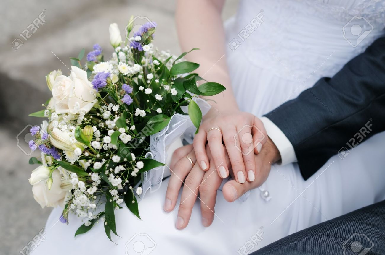 Bride And Grooms Hands With Wedding Rings And Bouquet Of Flowers