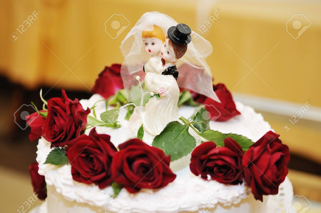 Figurines On Top Of Wedding Cake With Real Roses Decorations Stock