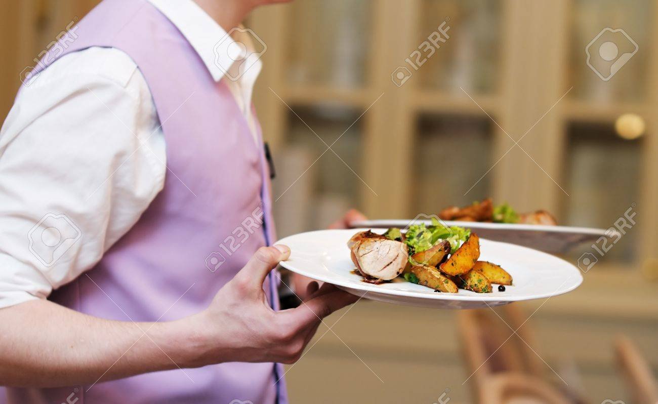 Waiter carrying two plate with meat and baked potato Stock Photo - 13248611