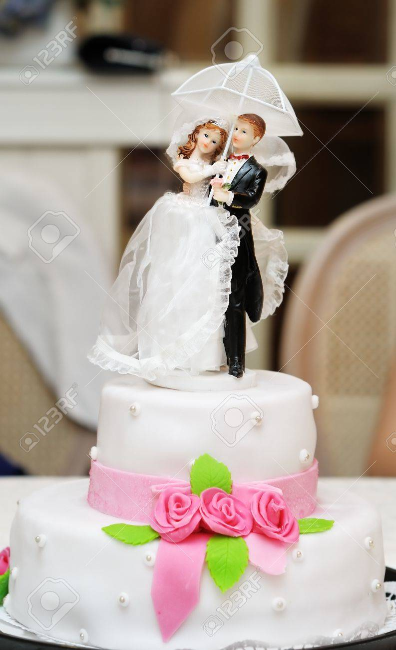 Figurines on top of wedding cake with roses decorations - 13443873