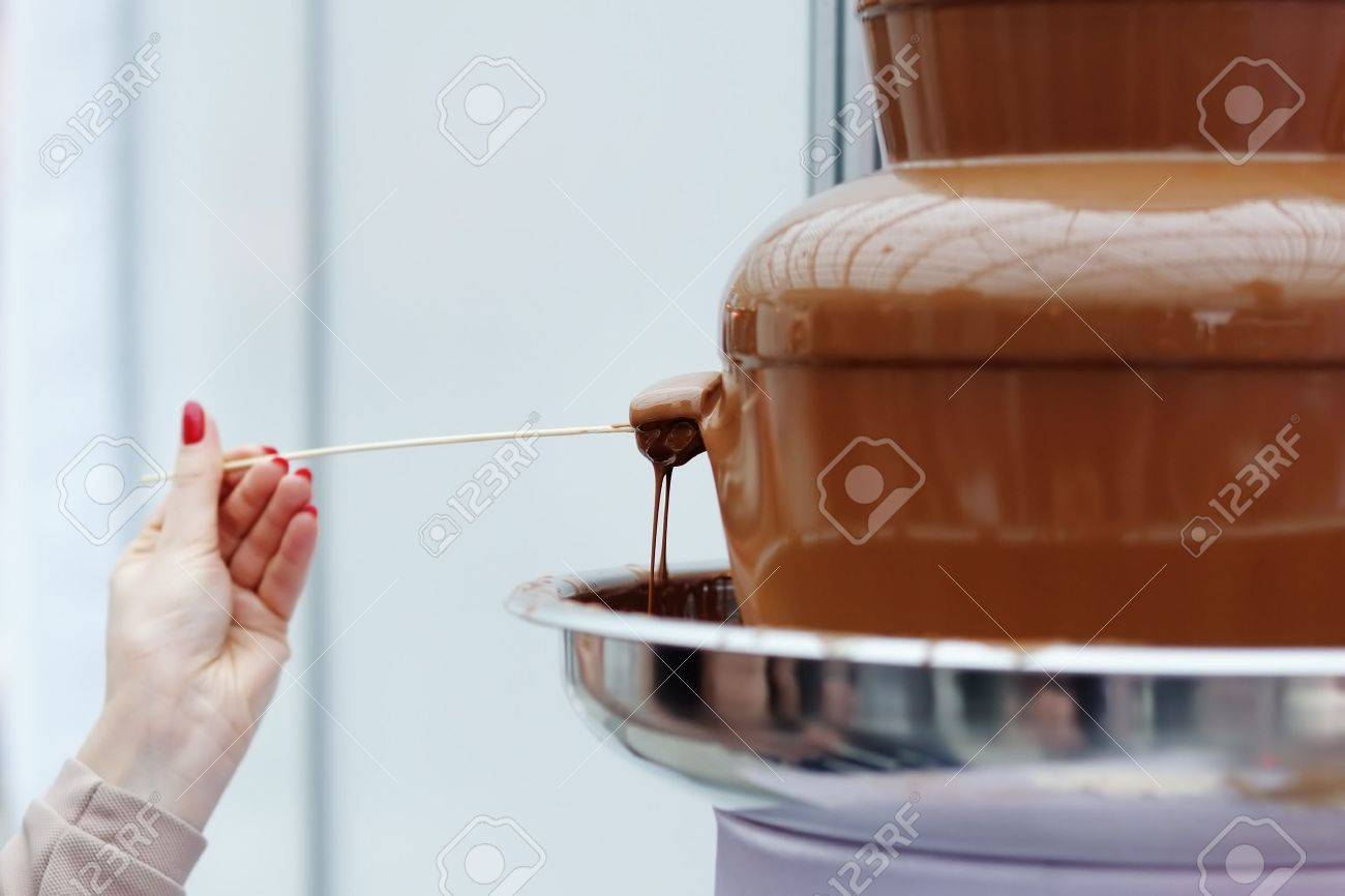 Marshmallow frosting in chocolate fondue fountain - 18937337