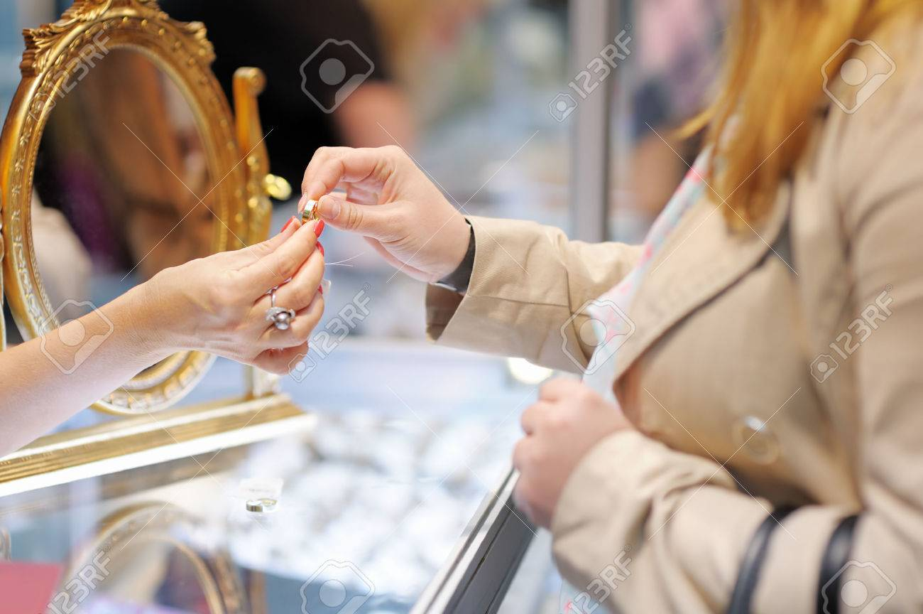 Woman trying wedding rings at a jeweler, focus on ring - 29263503