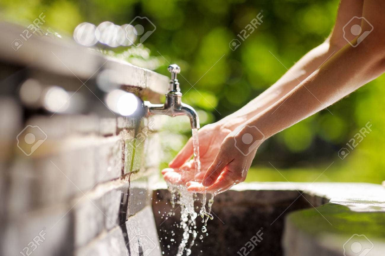 Closeup photo of woman washing hands in a city fountain - 31086674